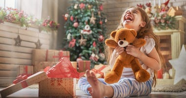 little girl gets a teddy bear for Christmas