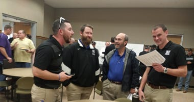 The assistant coaches at Vandegrift and Cedar Park meet up during the UIL Redistricting announcements