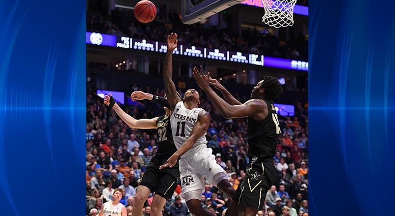 Texas A&M Aggies guard Wendell Mitchell (11) attempts to shoot the ball past Vanderbilt Commodores forward Matt Ryan (32) during the first half of the SEC conference tournament at Bridgestone Arena.
