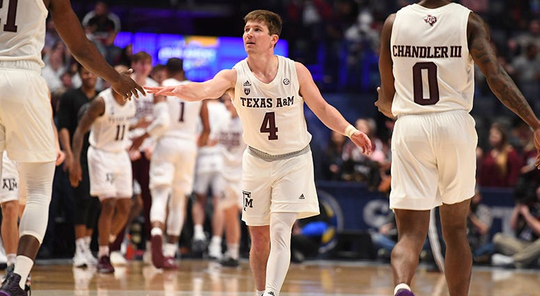 Texas A&M Aggies guard Mark French (4) celebrates with forward Christian Mekowulu (21) and guard Jay Jay Chandler (0) at the end of the first half of the SEC conference tournament at Bridgestone Arena.