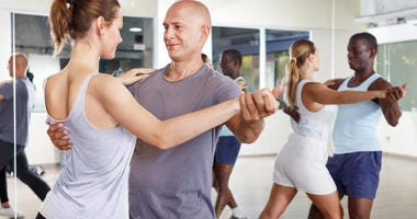 two couples ballroom dancing in a dance studio for fitness