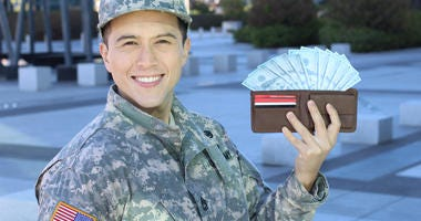military service woman holding open wallet with a fan of cash sticking out