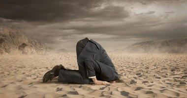 man wearing a suit with his head in the sand