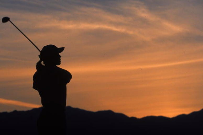 A silhouette of woman as she follows her shot