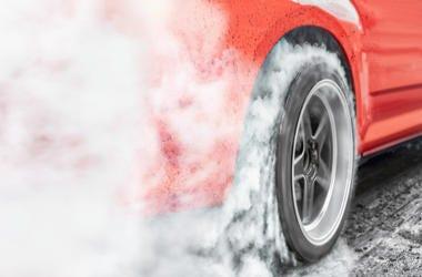 Racing car burns rubber off its tires