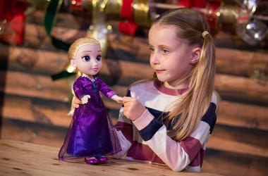 Girl plays with Frozen Elsa doll