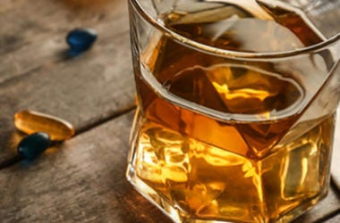 Glass of whisky with capsules