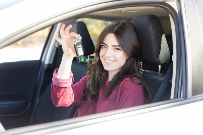 Woman smiling while showing key in car