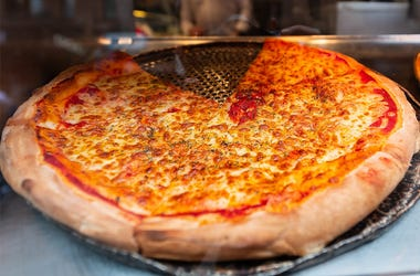 Closeup of fresh large crust pizza in store cafe on display restaurant in Italy with melted mozzarella cheese and plain tomato sauce slices - stock photo