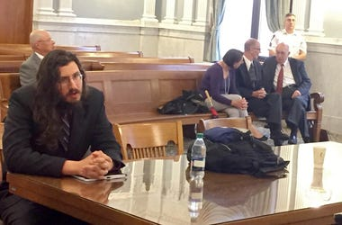Michael Rotondo, left, sits during an eviction proceeding in Syracuse, N.Y., brought by his parents, Mark and Christina, of Camillus. The two parents confer with their lawyer, Anthony Adorante, in the court gallery behind. Rotondo told the judge Tuesday,
