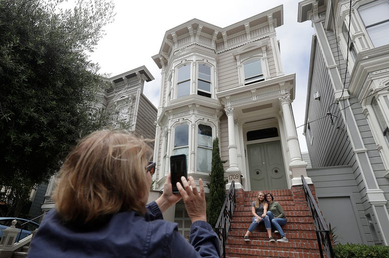 """Aries Layton, seated left, and her aunt Kelsy Layton pose as Debra Layton, Aries' grandmother and Kelsy's mother, foreground, takes photos outside a Victorian home made famous by the television show """"Full House"""" in San Francisco, Tuesday, July 17, 2018. T"""