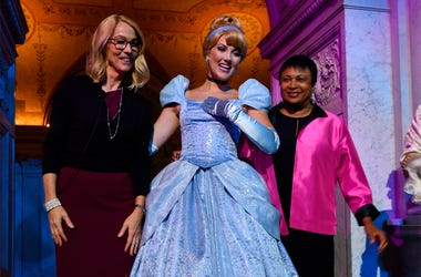 """Costumed Cinderella poses with Mary Walsh, left, managing director of the Disney Animation Research Library and Librarian of Congress Carla Hayden, right, at a ceremony marking the inclusion of Disney's """"Cinderella"""" into the National Film Registry on its"""