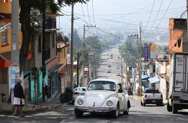 "A Volkswagen Beetle makes it to the top of a hill in a neighborhood of Mexico City known colloquially as ""Vocholandia,"" for its love of the classic Beetle, called vochos, Tuesday, July 9, 2019. (AP Photo/Cristina Baussan)"
