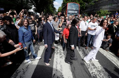 Fans dressed as lookalikes walk across the Abbey Road zebra crossing on the 50th anniversary of British pop musicians The Beatles doing it for their album cover of 'Abbey Road' in St Johns Wood in London. (Photo credit: AP Photo/Kirsty Wigglesworth)