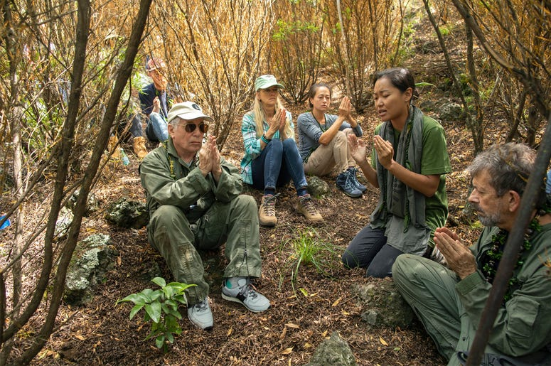 In this Friday, Aug. 16, 2019 photo, musician Paul Simon, left, joins in a prayer lead by Aimee Sato, second from right, prior to the planting of a lama tree at Auwahi Forest Reserve on Maui, Hawaii. (Anna Kim/Honolulu Star-Advertiser via AP)