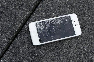 This Aug. 26, 2015 photo shows an Apple iPhone with a cracked screen after a drop test from the DropBot, a robot used to measure the sustainability of a phone to dropping, at the offices of SquareTrade in San Francisco. (AP Photo/Ben Margot, File)