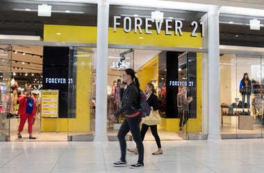 People walk in front of a Forever 21 clothing store, Monday, Sept. 30, 2019, in New York. (AP Photo/Mark Lennihan)
