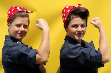 """Jessica Curtis and Sarah Neller pose for a photograph in front of a """"We Can Do It"""" backdrop as they joined with hundreds of women dressed as """"Rosie the Riveter"""" in an attempt to set a new Guinness World Record at Rosie the Riveter/WWII Home Front National"""
