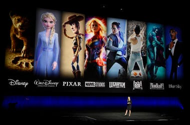 Characters from Disney and Fox movies are displayed behind Cathleen Taff, president of distribution, franchise management, business and audience insight for Walt Disney Studios. (Photo by Chris Pizzello/Invision/AP)