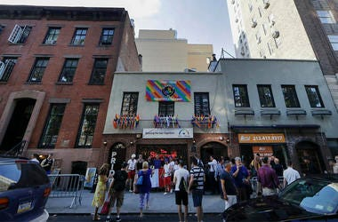 People gather near the Stonewall Inn Thursday, June 27, 2019, in New York. (AP Photo/Frank Franklin II)