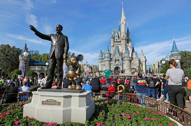 In this Jan. 9, 2019 file photo, guests watch a show near a statue of Walt Disney and Mickey Mouse in front of the Cinderella Castle at the Magic Kingdom at Walt Disney World in Lake Buena Vista, Florida. (AP Photo/John Raoux, File)