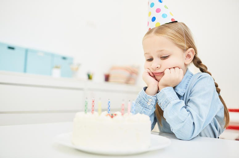 Sad birthday -  Sad little girl in birthday cap looking at festive cake with candles