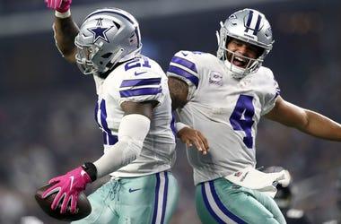 Ezekiel Elliott #21 and Dak Prescott #4 of the Dallas Cowboys celebrate the fourth quarter touchdown against the Jacksonville Jaguars at AT&T Stadium on October 14, 2018 in Arlington, Texas.
