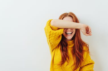 Smiling woman covering her eyes with her arm while waiting for a surprise