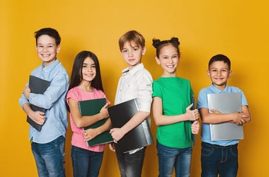 School kids with notebooks, standing in row and looking at camera over yellow background