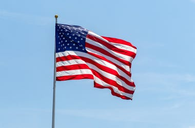 American flag waving on pole with bright vibrant red white and blue colors