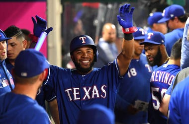 Elvis Andrus #1 of the Texas Rangers is greeted in the dugout after scoring a run in the sixth inning against the Los Angeles Angels at Angel Stadium on August 28, 2019 in Anaheim, California.