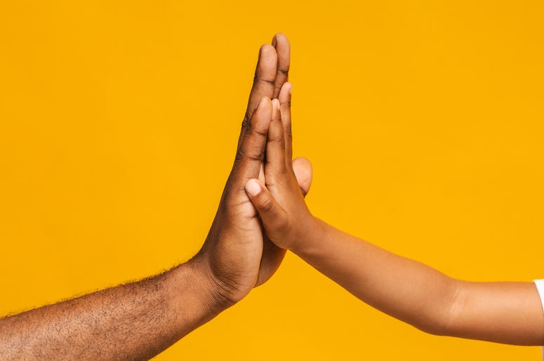 High five gesture of black father and child