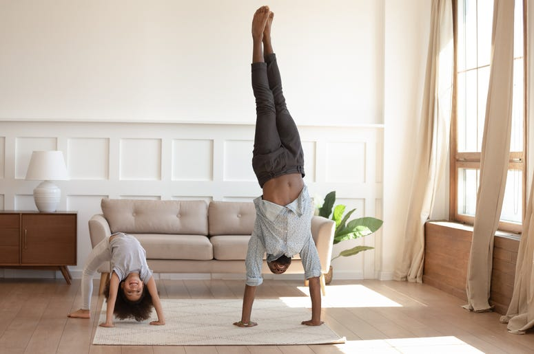 Happy african american girl doing bridge exercise, strong father staying on hands. Smiling black family doing morning exercises together in living room at home. Daily healthy habit concept.