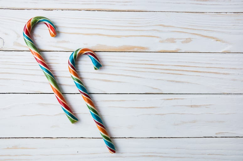 Colorful festive Lollipops on white wooden background selective focus top view