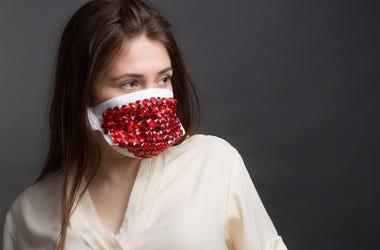 Studio portrait of Woman in protective mask with red rhinestones on a grey background