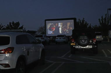 """Attendees watch the movie """"The Goonies"""" at a pop-up drive-in theatre built in the parking lot at the Broadway Commons on May 21, 2020 in Hicksville, New York."""