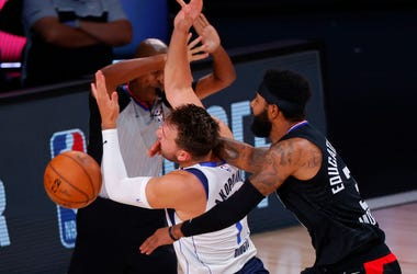 Marcus Morris Sr. #31 of the LA Clippers fouls Luka Doncic #77 of the Dallas Mavericks during the first quarter in Game Six of the Western Conference First Round during the 2020 NBA Playoffs at AdventHealth Arena at ESPN Wide World Of Sports Complex.
