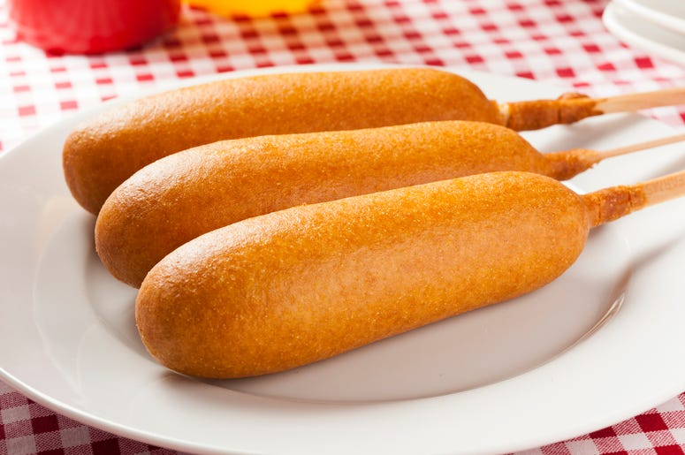 Corn dogs with ketchup and mustard on white background