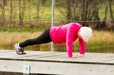 Grandmother is working out by plank exercise.