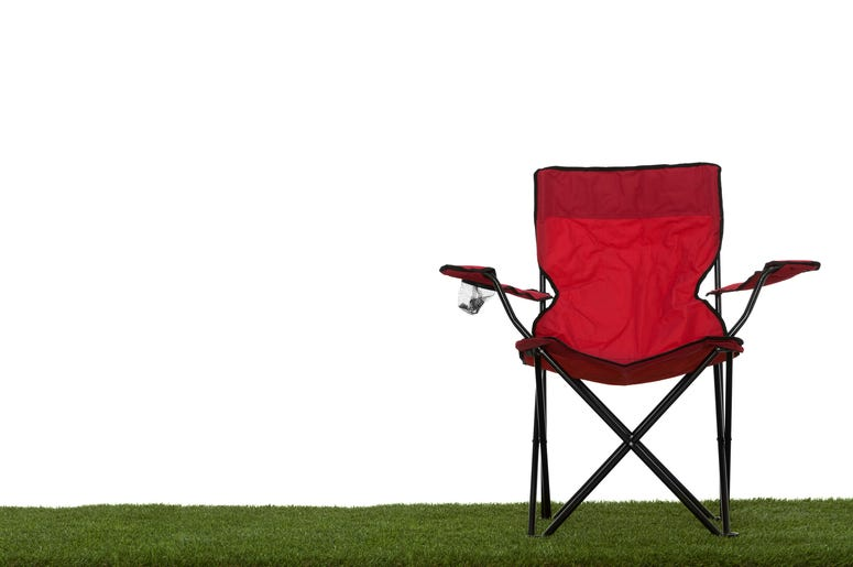 Folding camp chair front view on grass with white background