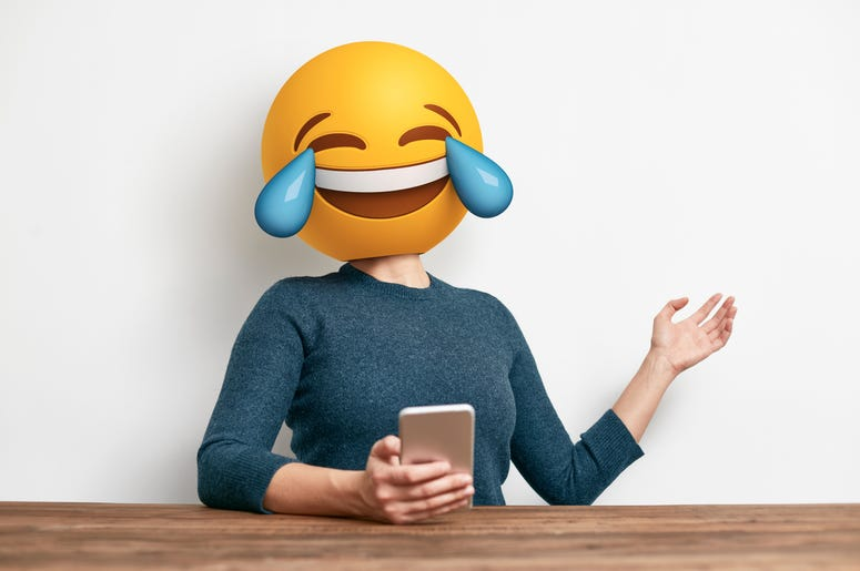 Emoji Head Woman sitting at desk. Woman wearing tears of joy emoji masks while looking at her phone. This emoji is laughing so much that it is crying tears of joy