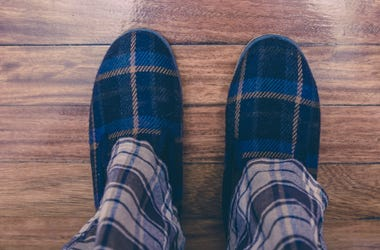 Man wearing pajamas and slippers on hardwood floor