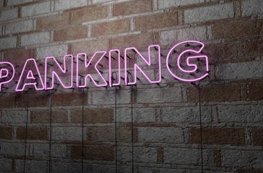 SPANKING - Glowing Neon Sign on stonework wall - 3D rendered royalty free stock illustration