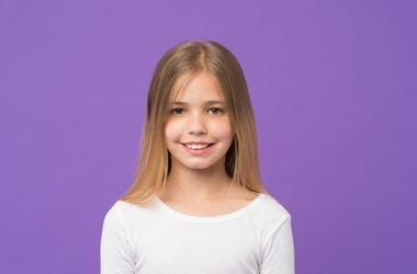Girl with beautiful smile isolated on purple background. Child with cute face studio portrait. Model with shining blonde
