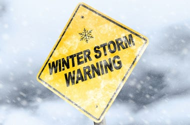 Winter Storm Warning Sign With Snowfall and Stormy Background.