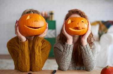 Two women showing Halloween pumpkins
