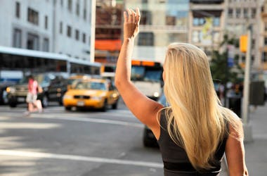 Blonde woman flags down taxi cab in New York City