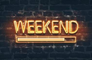 Weekend loading neon sign on dark brick wall background