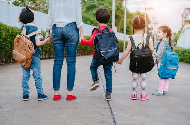 Motherl and kids holding hands going back to school with backback.
