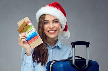 Smiling woman traveler wearing christmas hat holding passport